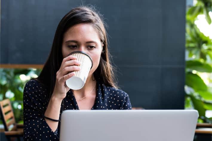 Kvinde der browser på en bærbar pc, mens hun nipper til kaffen
